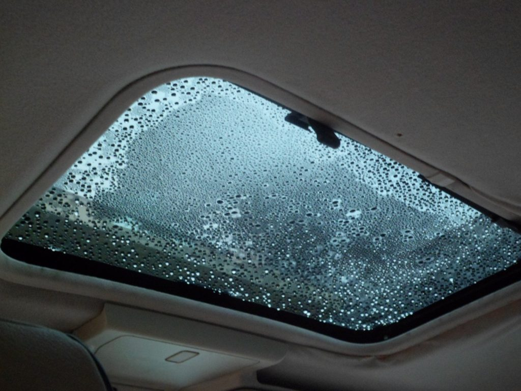 A car sunroof with excessive moisture on it
