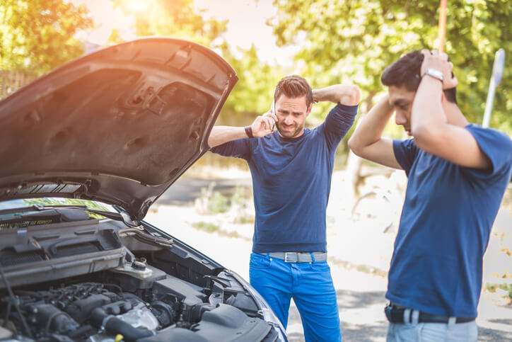 Two men look concerned with hands on the back of their heads as they look at a broken down car with the hood propped open.