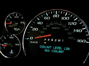 A dashboard shows a coolant warning message: 'Coolant level low - add coolant'.