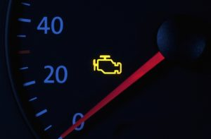 A 'check engine' light glows on a car dashboard.